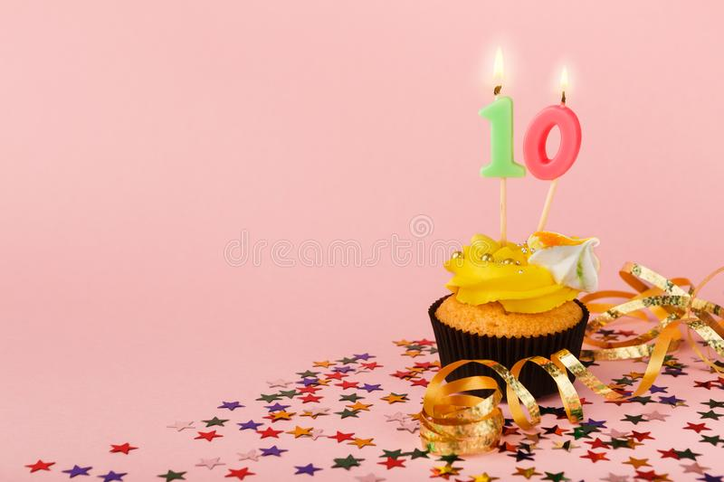 Tenth birthday cupcake with candle and sprinkles. On pink background. Card mockup, copy space. Birthday, party, holiday concept stock photography