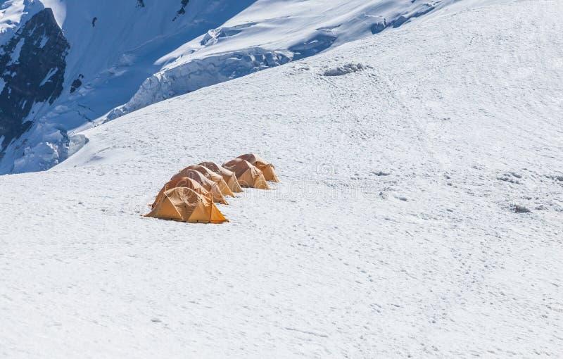 Tents at Lenin peak camp 3, 20000 ft, at mt. Razdelnaya. Pamir mountains. Kyrgyzstan stock photography