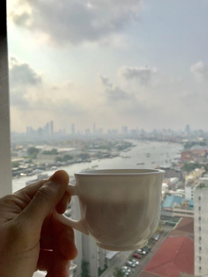 tenu dans la main une tasse de café, fond de rivière de chaopraya images libres de droits