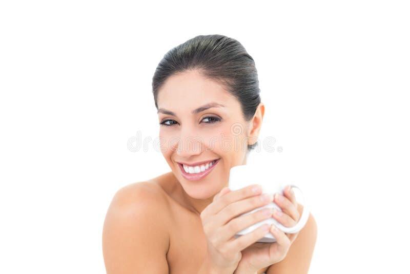 Tenuta abbastanza castana una tazza bianca e sorridere alla macchina fotografica fotografie stock