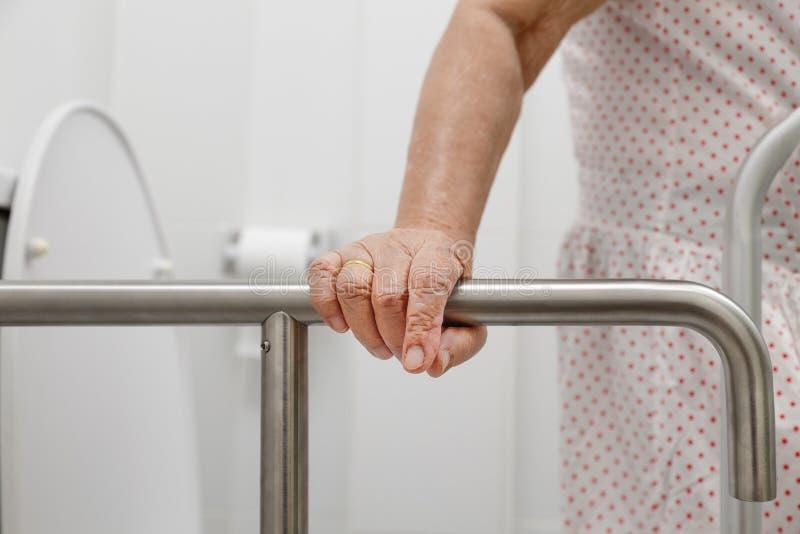 Tenuta anziana della donna sul corrimano nella toilette immagini stock libere da diritti