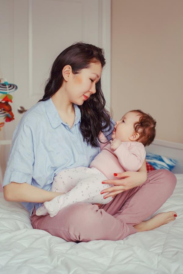 Tenuta asiatica della madre della corsa mista che tocca abbracciando il suo bambino infantile neonato adorabile sveglio fotografia stock