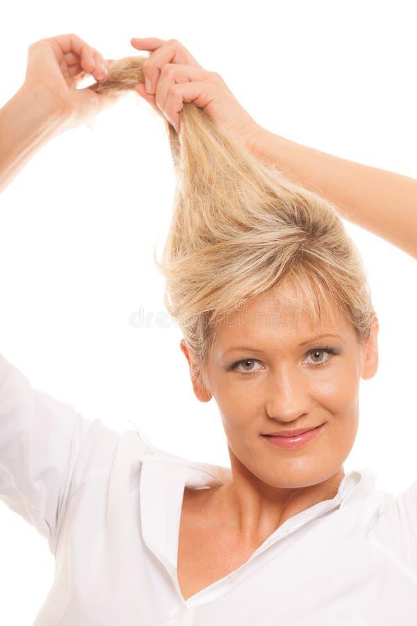 Tenuta bionda della donna matura del ritratto i suoi capelli lunghi fotografia stock libera da diritti