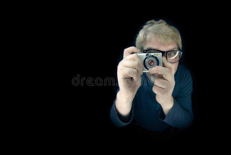 Tenuta bionda divertente dell'uomo una macchina fotografica d'annata ed indicarla alla macchina fotografica - isolata sul nero immagine stock