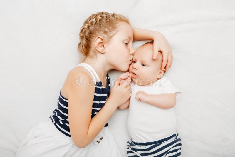 Tenuta caucasica della sorella della ragazza che bacia piccolo bambino, trovantesi sul letto fotografie stock libere da diritti