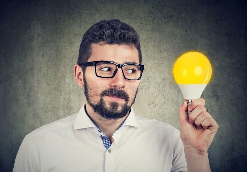 Tenuta curiosa dell'uomo che esamina la lampadina della luce intensa fotografia stock