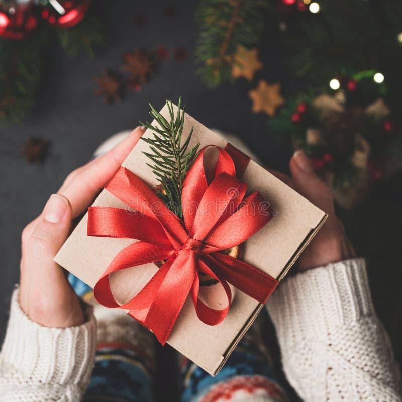 Tenuta del contenitore di regalo di Natale con pizzo rosso fotografia stock libera da diritti