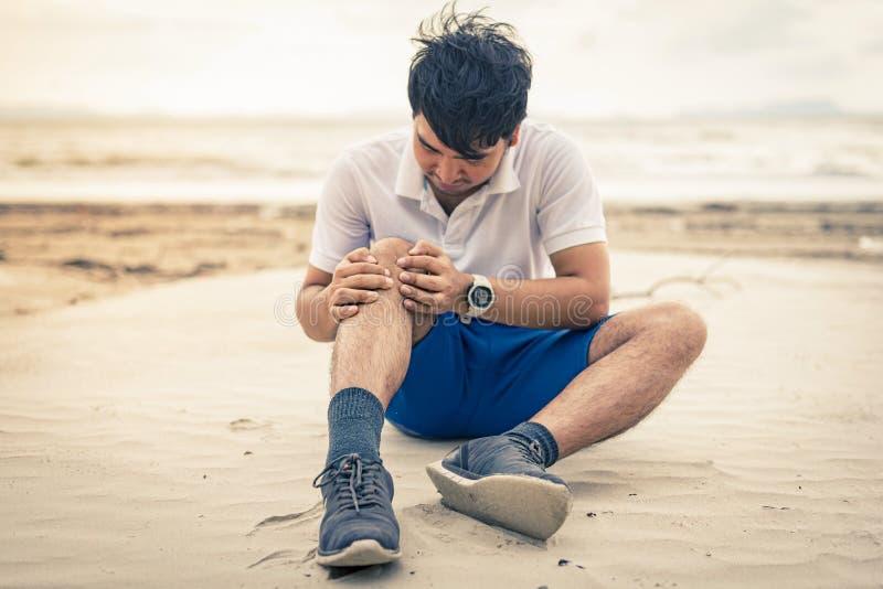 Tenuta del corridore dell'uomo il suo ginocchio nel dolore sui precedenti della spiaggia fotografia stock