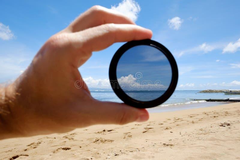 Tenuta del filtro polarizzatore contro la spiaggia che dà chiarezza fotografie stock libere da diritti