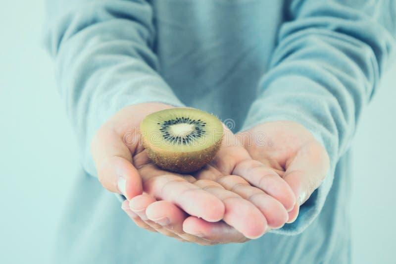 Tenuta del kiwi fresco sulle mani immagini stock libere da diritti