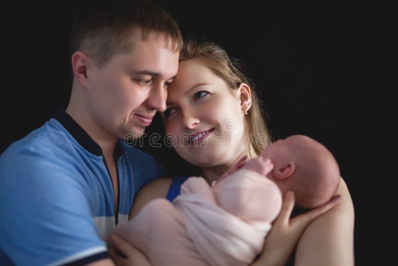 Tenuta del padre e madre un bambino, concetto neonato di cura della famiglia fotografia stock