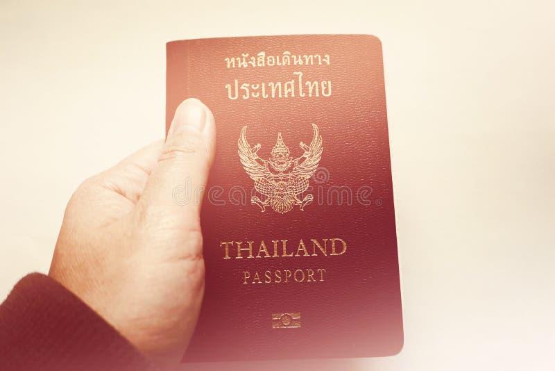 Tenuta del passaporto tailandese valido fotografia stock