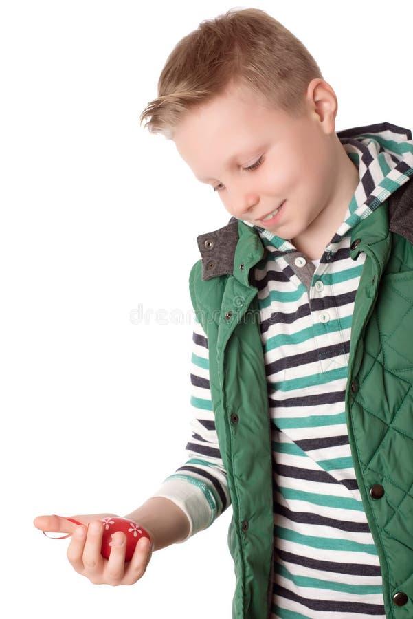 Tenuta del ragazzo dell'adolescente un uovo di Pasqua rosso in sua mano fotografia stock libera da diritti