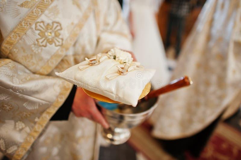 Tenuta del sacerdote un piccolo cuscino con le fedi nuziali a cerimonia della chiesa fotografia stock libera da diritti