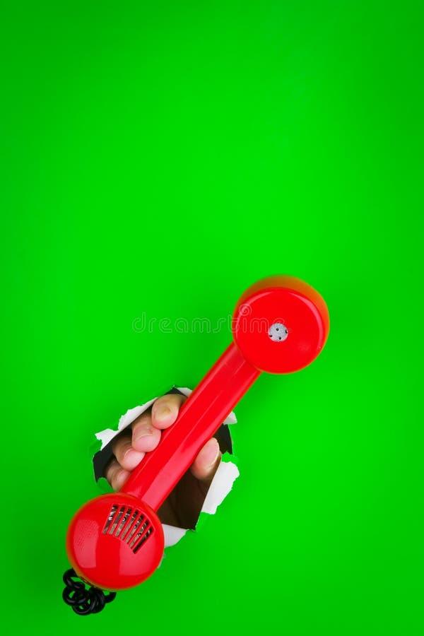 Tenuta del telefono rosso fotografia stock