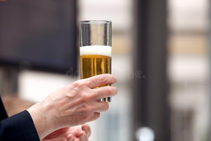 Tenuta del vetro di birra fotografia stock