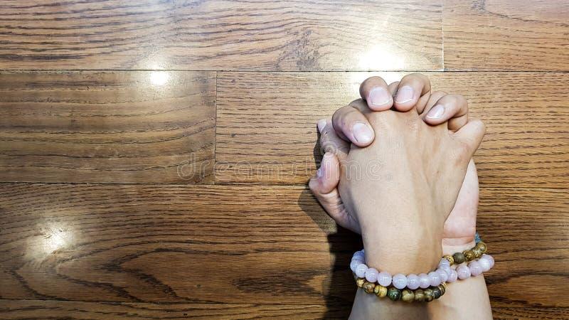 Tenuta dell'amante mano sulla tavola di legno fotografie stock