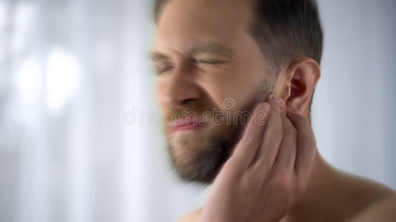 Tenuta dell'uomo che danneggia i problemi dell'orecchio, di otite o dell'otorinolaringoiatra di infezione, fine su immagini stock