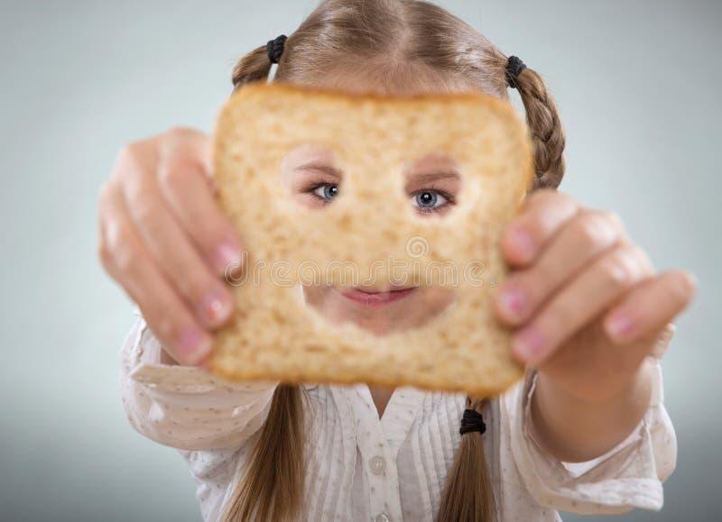 Tenuta della bambina davanti al suo fronte, una fetta di pane felice fotografia stock libera da diritti