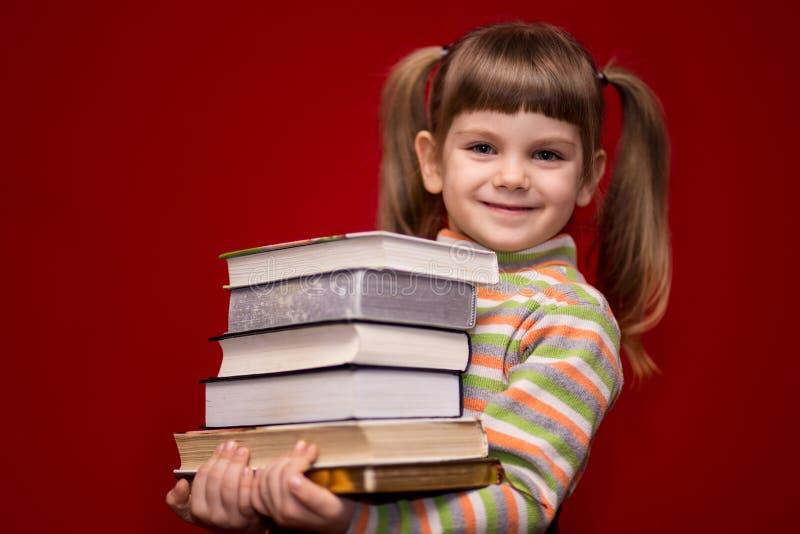 Tenuta della bambina molti libri isolati su rosso fotografia stock