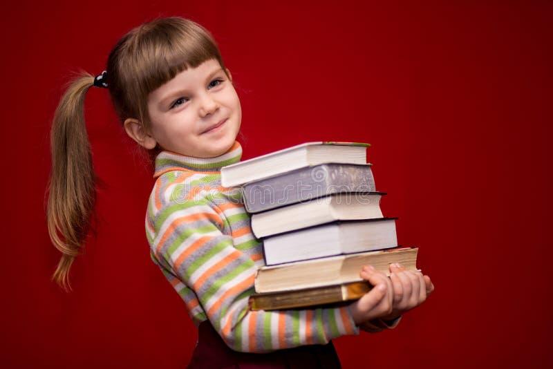 Tenuta della bambina molti libri isolati su rosso immagine stock