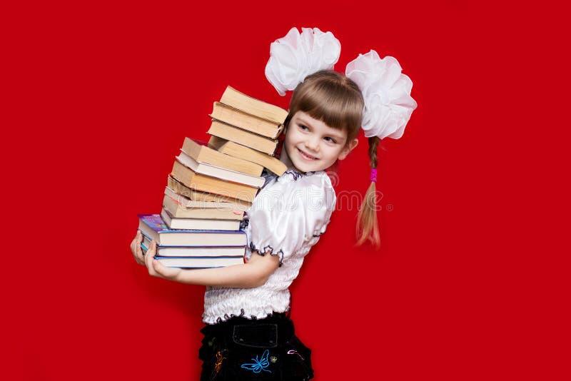 Tenuta della bambina molti libri isolati su rosso fotografie stock