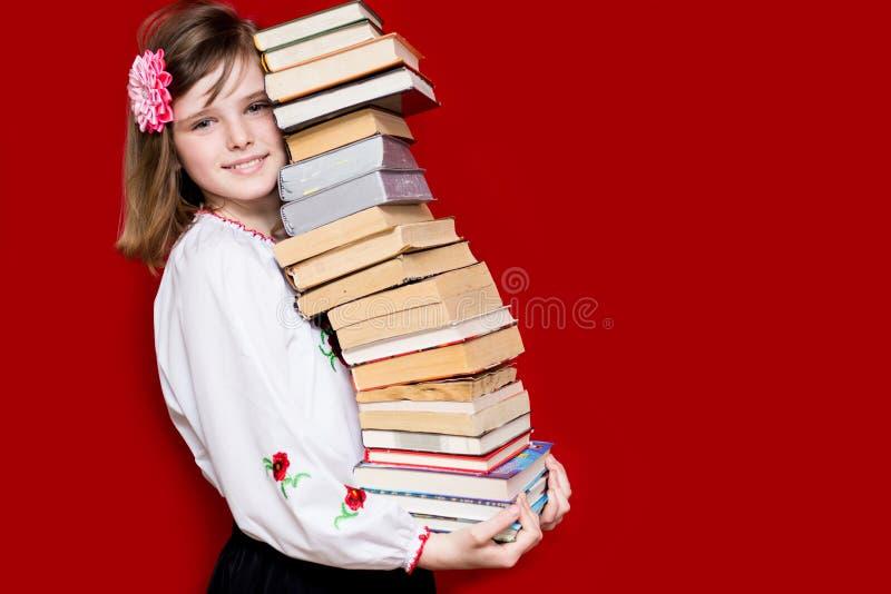 Tenuta della bambina molti libri su rosso immagini stock