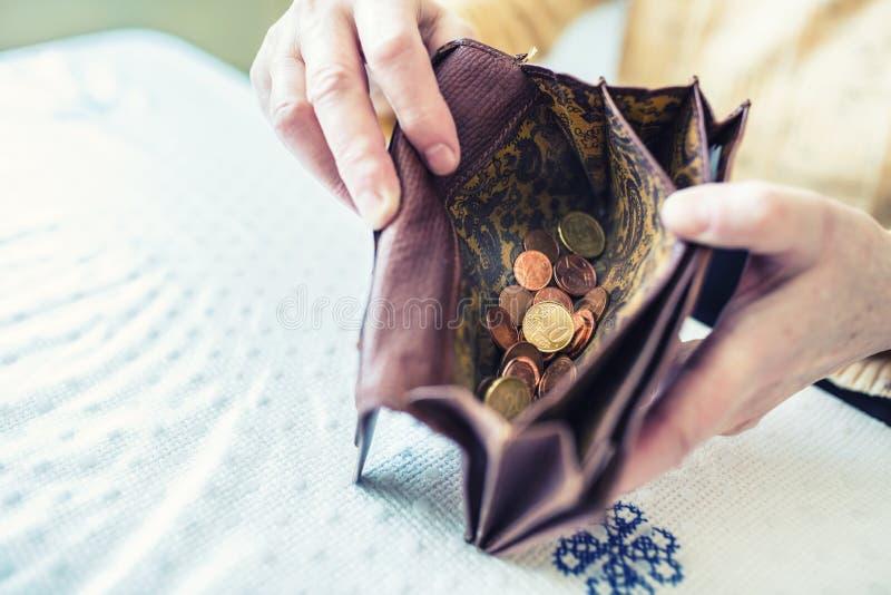 Tenuta della donna del pensionato in portafoglio delle mani con le euro monete fotografia stock libera da diritti