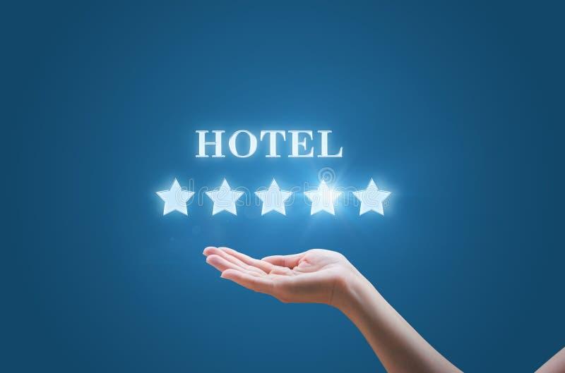 Tenuta della donna di affari nel suo stelle della mano cinque e l'iscrizione l'hotel fotografie stock libere da diritti