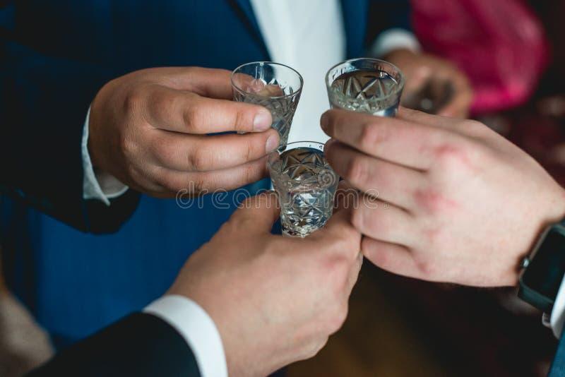 Tenuta della gente in vetri di mani con alcool Festa nuziale immagine stock