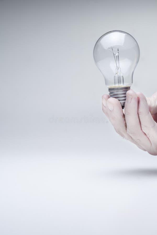 Tenuta della lampadina con la mano immagine stock
