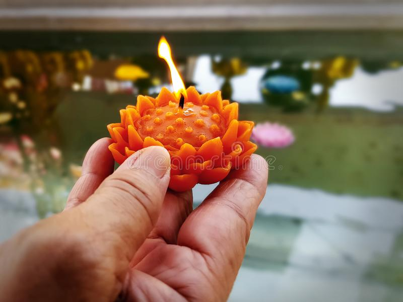 Tenuta della mano che brucia la candela arancio del fiore in Front Of Water Bath immagine stock