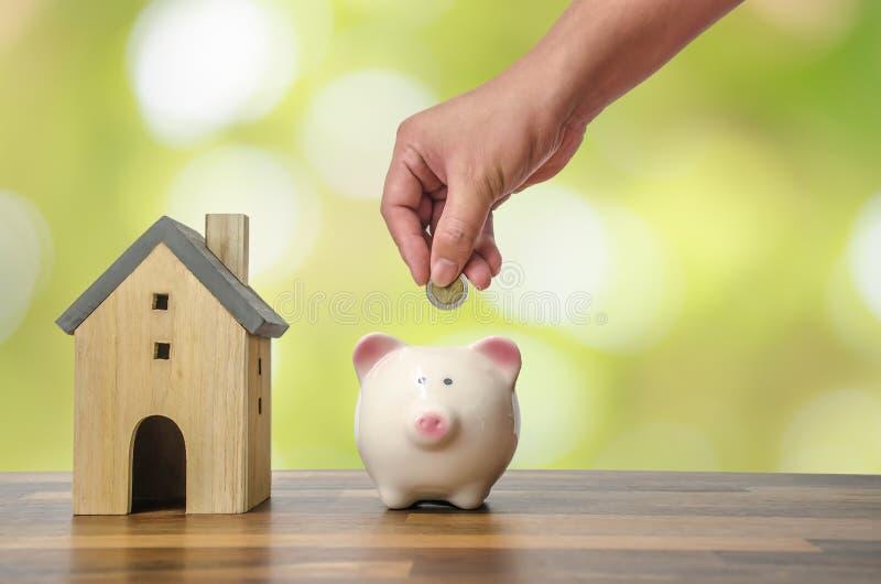 Tenuta della mano dell'investitore una moneta con i risparmi nel porcellino salvadanaio messo sui soldi sul modello domestico per fotografia stock libera da diritti
