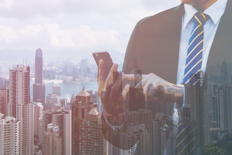 Tenuta della mano dell'uomo d'affari di doppia esposizione e Smart Phone del touch screen con il fondo moderno della città Cellul fotografie stock libere da diritti