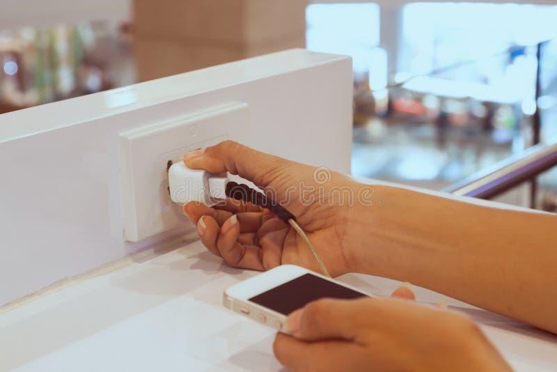 Tenuta della mano della donna il cavo di carico che tappa lo Smart Phone immagine stock
