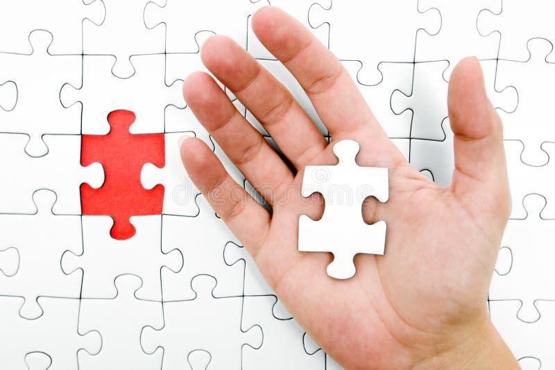 Tenuta della parte del puzzle fotografia stock