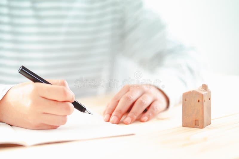 Tenuta della penna stilografica dall'uomo con il piccolo modello domestico ceramico sullo scrittorio immagini stock libere da diritti