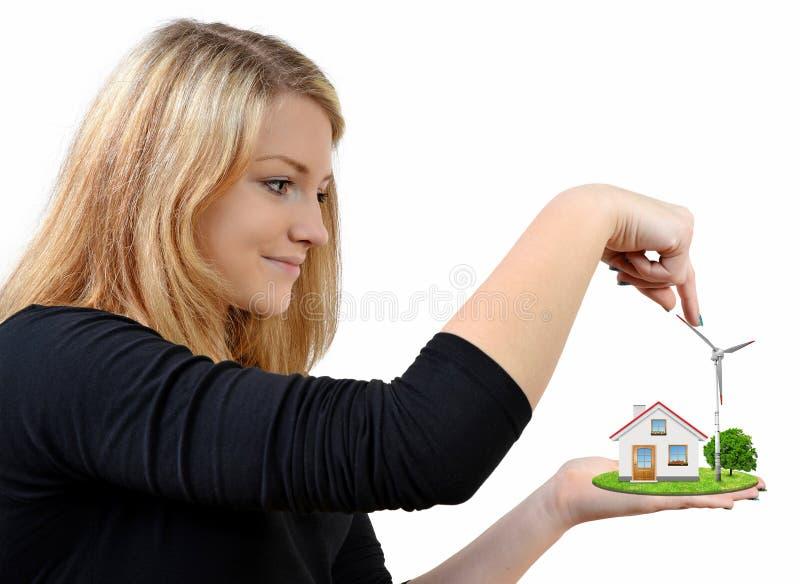 Tenuta della ragazza in generatore eolico delle mani con la casa fotografia stock