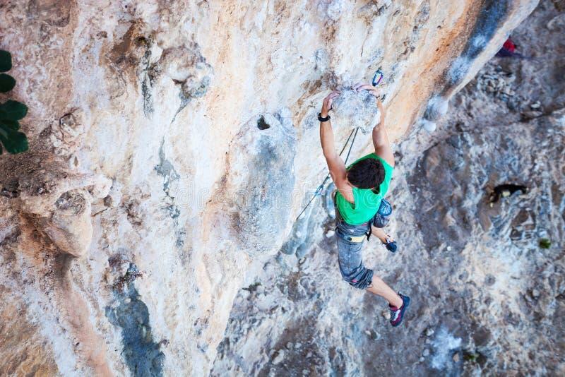Tenuta dello scalatore sulla maniglia mentre scalando scogliera fotografie stock