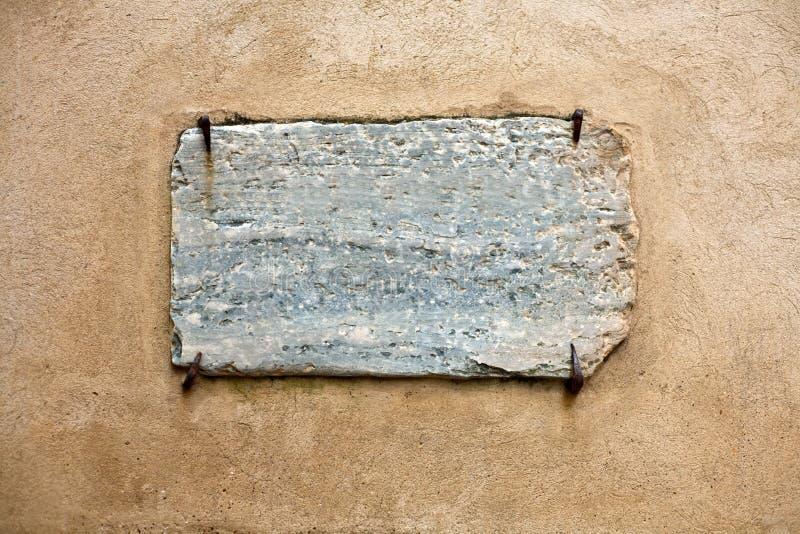 Tenuta di marmo dell'insegna dai chiodi arrugginiti fotografia stock libera da diritti