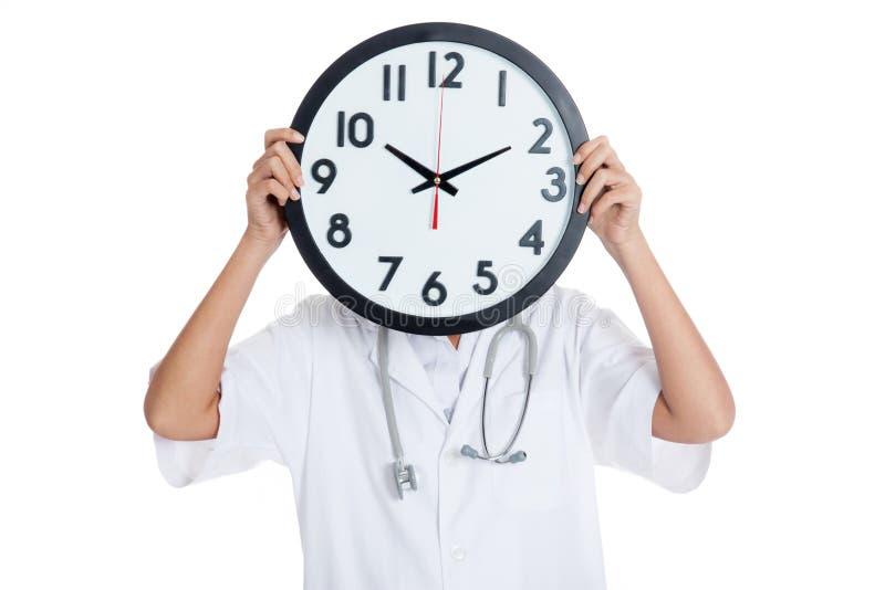 Tenuta di medico un orologio sopra il suo fronte fotografie stock