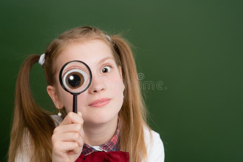Tenuta divertente della ragazza sulla lente di ingrandimento della lente d'ingrandimento dell'occhio immagini stock libere da diritti