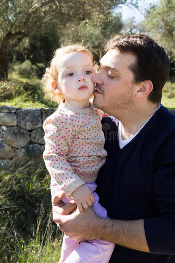 Tenuta felice del padre sulla piccola figlia delle mani fotografia stock