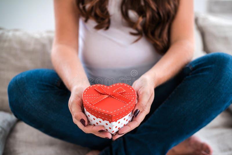 Tenuta felice della donna incinta un contenitore di regalo immagine stock