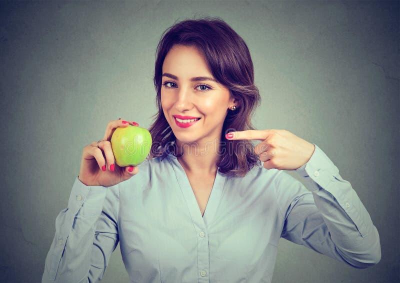 Tenuta felice della giovane donna che indica alla mela verde fotografia stock libera da diritti