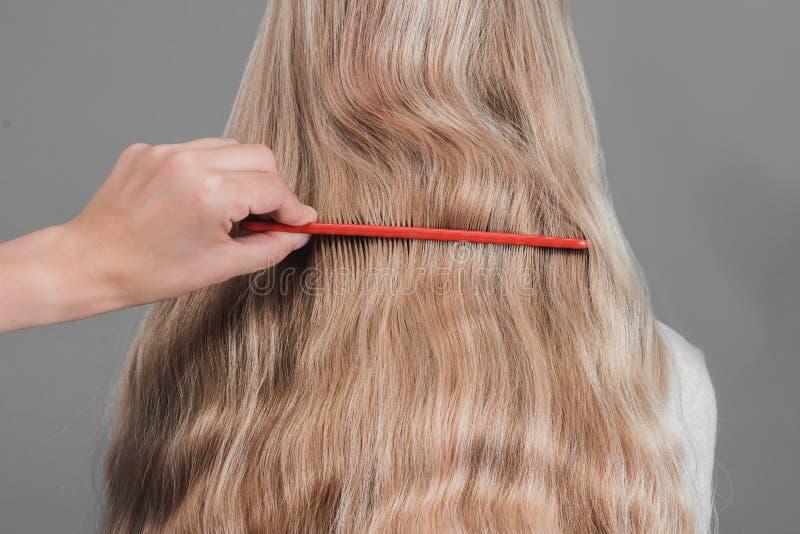 Tenuta femminile del parrucchiere a disposizione fra la serratura delle dita di capelli biondi, il pettine ed il primo piano di f immagine stock libera da diritti