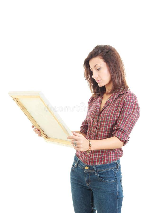 Tenuta graziosa della donna ed esaminare la pittura di arte nello studio immagine stock libera da diritti
