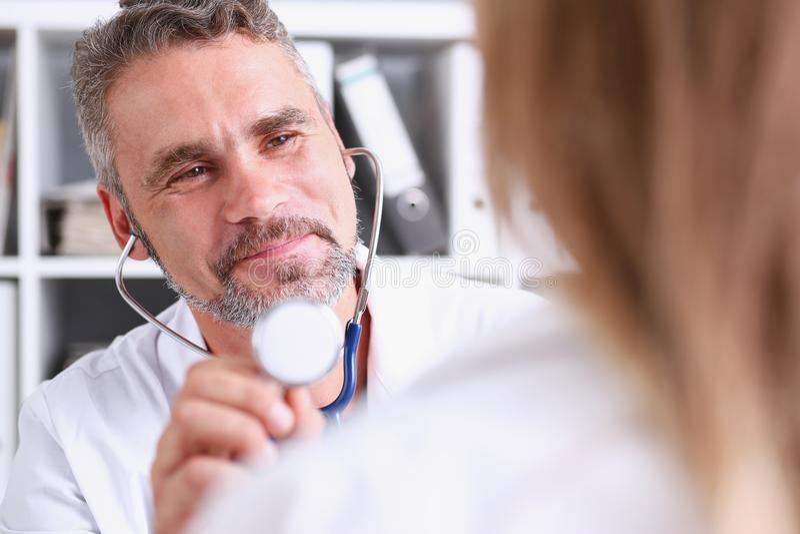 Tenuta matura bella di medico in testa dello stetoscopio del braccio immagine stock