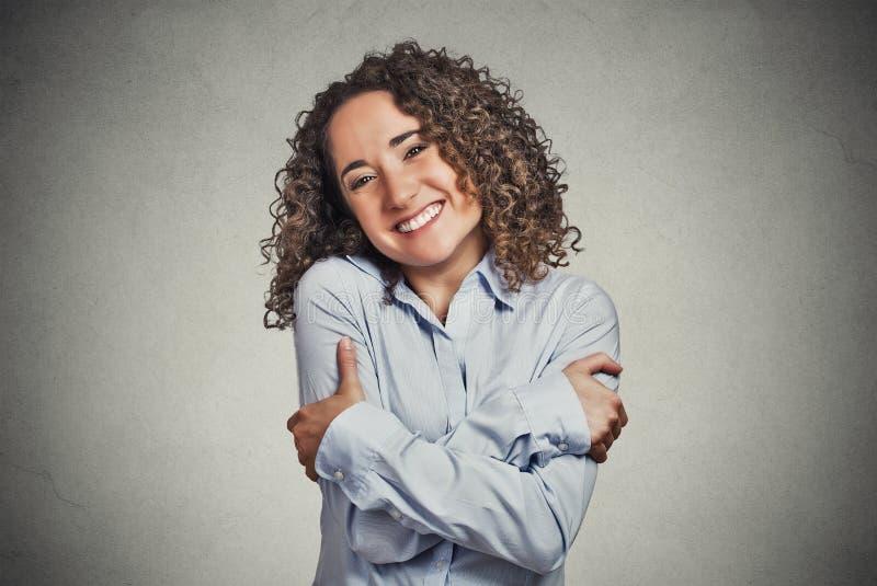 Tenuta sorridente della donna che si abbraccia fotografie stock libere da diritti