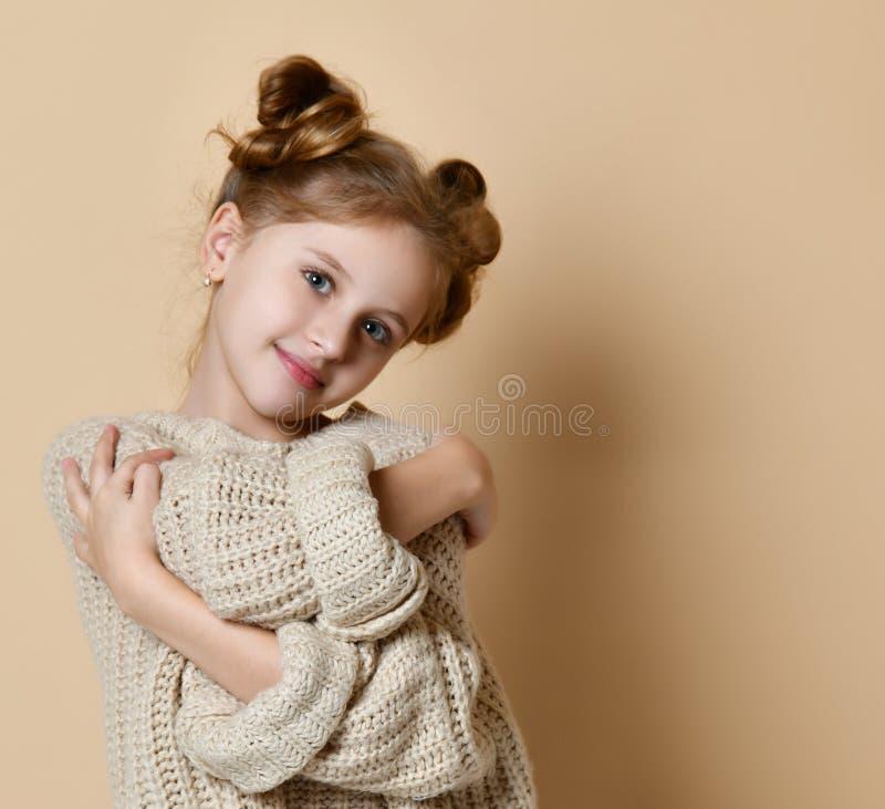 Tenuta sorridente della ragazza del ritratto alto vicino che si abbraccia fondo nudo isolato della parete immagini stock